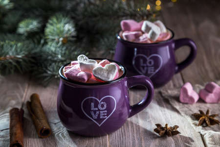 Coffee with marshmallows in the shape of a heart in a cup, cinnamon and star anise on a wooden background.