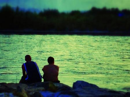 beside: Two men sitting beside a lake