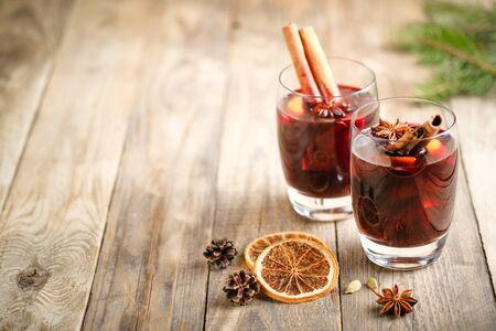 Glühwein in Glasgläsern mit Äpfeln, Orange, Zimt und Sternanis. Heißes Weihnachtsgetränk auf dunklem Hintergrund mit einem Tannenzweig-Kopienraum.