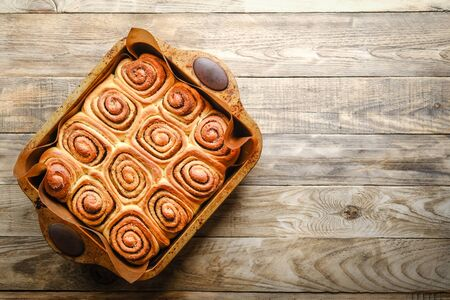 Fresh homemade cinnabons baked in metal form on a light rustic background top view. Homemade baking.