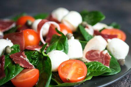 Salad with prosciutto, mozzarella, cherry tomatoes, capers and spinach on a dark plate on a dark background top view copy space.