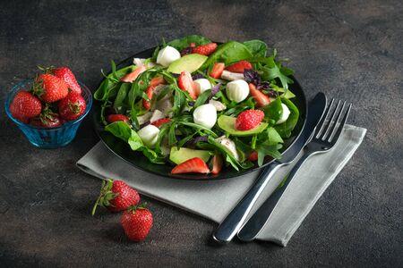 Salad with fresh strawberries, mozzarella, chicken, avocado and fresh herbs on a dark plate on a dark background.