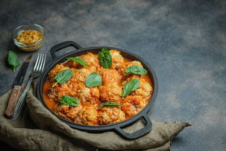 Meatballs in a pan with spinach leaves on a dark background copy space.