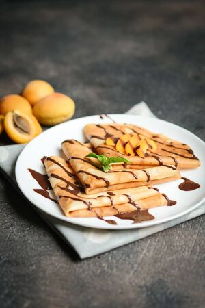 Crepes with chocolate sauce, fruits and mint on a dark background.