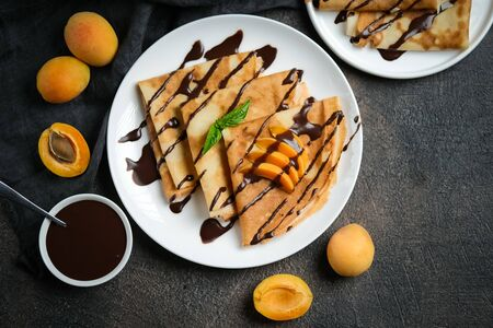Crepes with chocolate sauce, fruits and mint on a dark background top view.