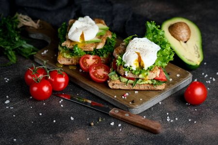 Delicious sandwich with avocado and poached egg, with green leaves and tomatoes on a dark background. Healthy breakfast.
