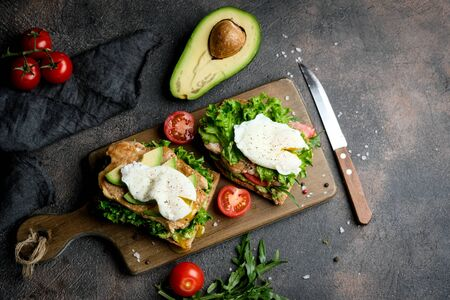 Delicious sandwich with avocado and poached egg on a dark background. Healthy breakfast. Top view. 写真素材