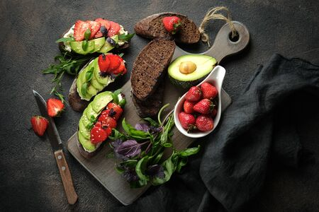 Toast or sandwich with avocado, cheese, strawberries, herbs and seeds on a dark background. An idea for bruschetta or for a healthy snack. Healthy vegan breakfast.Top view.