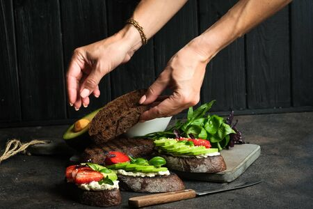 Toast or sandwich with avocado, cheese, strawberries, herbs and seeds on a dark background. Female hands serve a dish. An idea for bruschetta or for a healthy snack. Healthy vegan breakfast. 写真素材