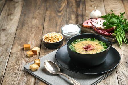 Sopa de guisantes con tocino, hierbas y pan rallado en un espacio de copia de fondo rústico.