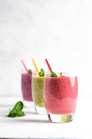 Colorful smoothie, fresh vitamins drink with raspberry, kiwi, banana and blueberries. Healthy detox vitamin diet or vegan food concept on a light background. Copy space. Фото со стока