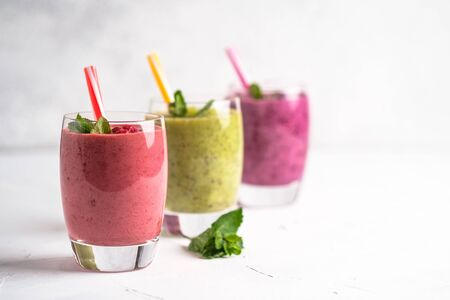 Colorful smoothie, fresh vitamins drink with raspberry, kiwi, banana and blueberries. Healthy detox vitamin diet or vegan food concept on a light background. Copy space.