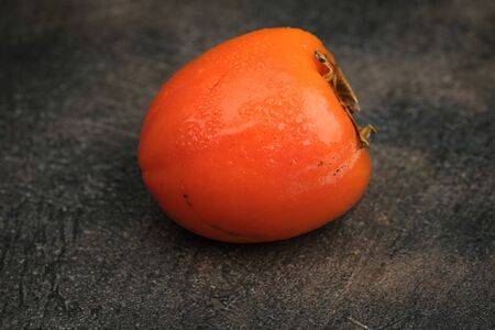 Frozen ripe persimmon fruit isolate on a dark background free copy space top view.