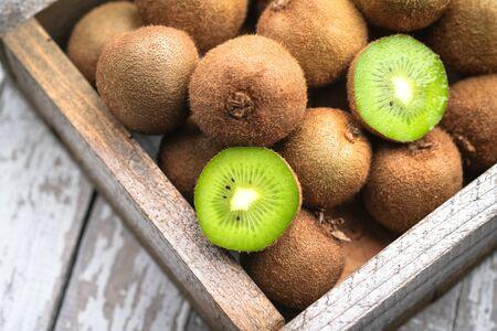 Ripe fresh kiwi fruits in wooden box on rustic background.