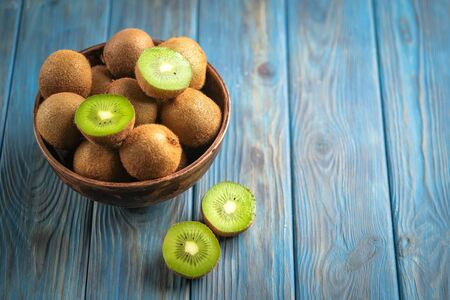 Kiwi fruit  in bowl on  blue wooden rustic table, ingredient for detox smoothie.