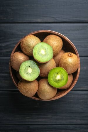 Kiwi fruit in a bowl on wooden dark table, ingredient for detox smoothie. Top view. Stock Photo