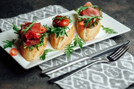 Traditional italian bruschetta with tomatoes, prosciutto, cream cheese and arugula in white ceramic plate on a dark background.