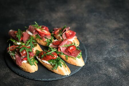 Traditional italian bruschetta with tomatoes, prosciutto, cream cheese and arugula on stone dish on a dark background with copy space