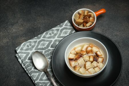 Hearty lunch. Meat broth or bouillon  from veal with breadcrumbs on a dark background. Фото со стока