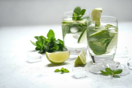 Refreshing mojito cocktail with mint, rum and lime, cold drink or beverage with ice on white background. Archivio Fotografico