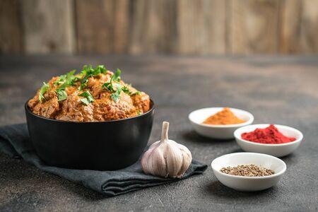 Pollo tikka masala cibo a base di carne piccante asiatico tradizionale con riso pomodori e coriandolo in una ciotola nera su sfondo scuro.