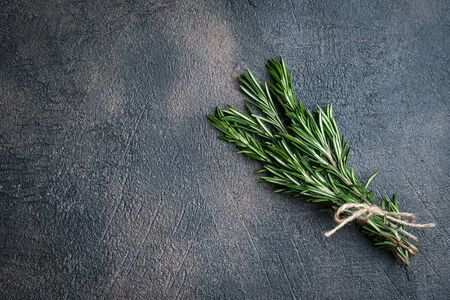 Bunch of fresh rosemary on a black background.Top view with copy space.