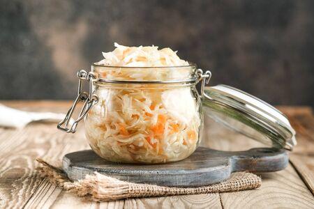 Chucrut casero con especias en un frasco de vidrio sobre un fondo rústico. Producto fermentado.