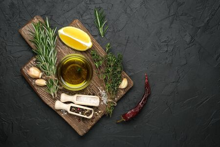 Selected ingredients for cooking. Lemon, herbs, olive oil and spices on a cutting board on a dark stone background.  Top view copy space.