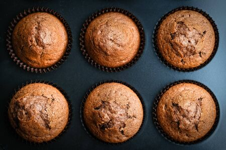 Various homemade muffins in a baking dish with berries, chocolate and mint on a dark background top view copy space.
