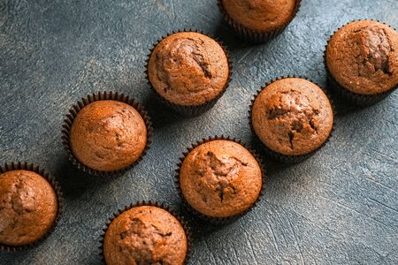 Chocolate and vanilla muffins on a portioned board on a dark background top view copy space.