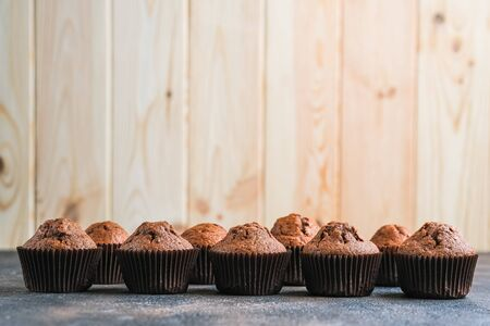 Chocolate and vanilla muffins on a portioned board on a dark background copy space.