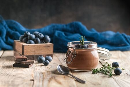 Chocolate mousse in glass jar with berries on a rustic background copy space. Homemade dessert.