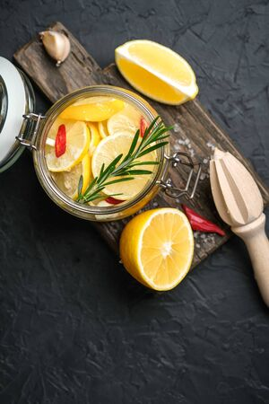 Salted lemons in glass jar on a dark background. Moroccan cuisine.