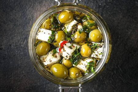 Feta with olives marinated in olive oil with spices. Meze is a dish of Mediterranean cuisine top view copy space.