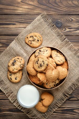 Mix of cookies in a wooden box with milk on rustic background.
