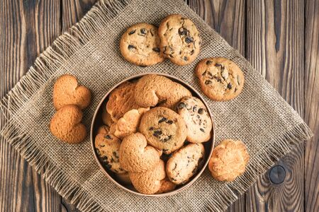 Mix of cookies in a wooden box on rustic background copy space.