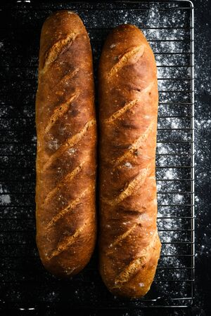 Traditional french baguettes on a dark background top view copy space.
