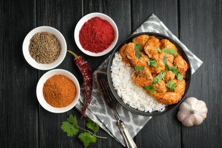 Chicken tikka masala traditional Asian spicy meat food with rice tomatoes and cilantro in a black bowl on dark background. 版權商用圖片