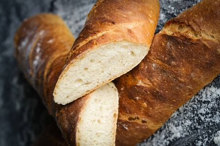 Traditional french baguette with flour on a dark background close-up.