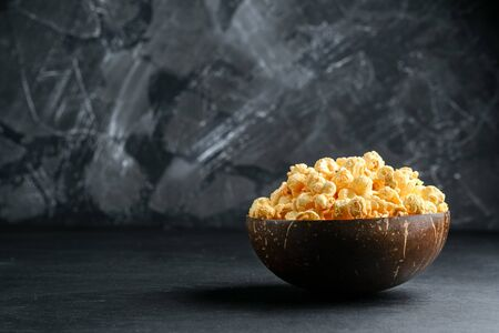 Cheesy popcorn in a coconut bowl on a dark background copy space.