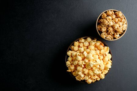 Popcorn. Cheese and caramel popcorn on a dark background. Top view copy space.
