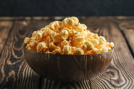Cheesy popcorn in a coconut bowl on a rustic background copy space. 版權商用圖片