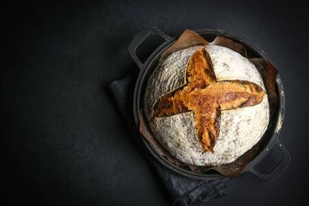 Bread. Homemade whole grain bread and baking dish on a dark background copy space.
