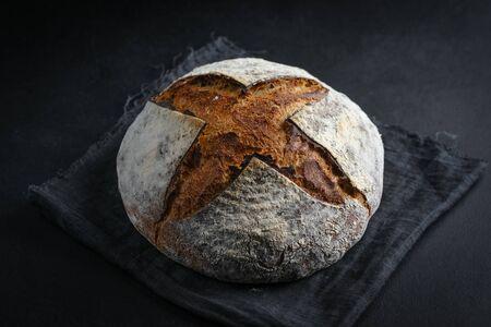 Bread. Homemade whole grain bread on a dark napkin on a dark background copy space.