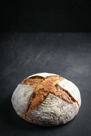 Homemade whole grain bread on a dark background copy space .