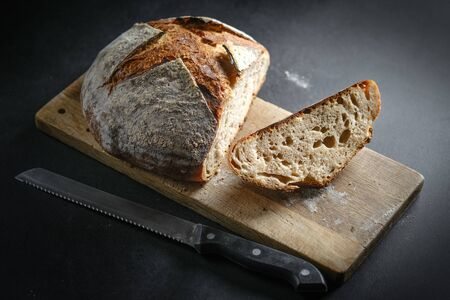 Bread. Homemade sliced whole grain bread on a cutting board with a knife on a dark background copy space. 版權商用圖片