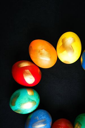 Painted eggs on a dark background top view copy space. Easter theme.
