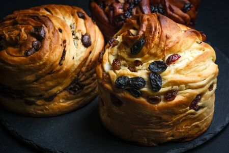 Cruffins with dried fruits, chocolate and black currants on a dark background. 版權商用圖片