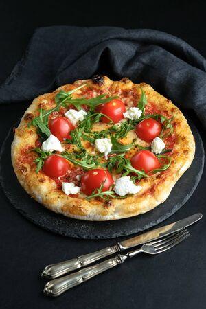 Homemade pizza with mozzarella, parmesan, chorizo and arugula on a dark background.