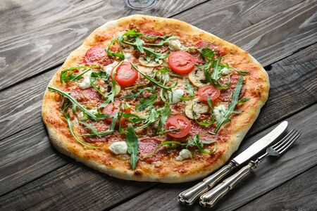 Homemade pizza with mozzarella, parmesan, chorizo, mushrooms and arugula on a rustic background top view copy space.
